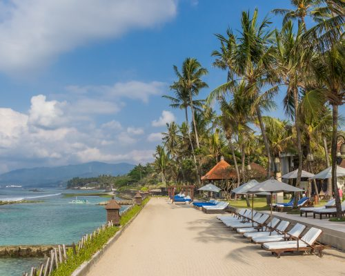 Sunbeds under palm trees at the Candidasa coast of Bali, Indonesia