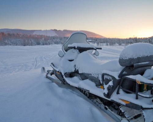 Snowmobile parked in Levi, Finland after sunset