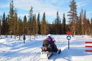 Person on a snow mobile on a track with a snow mobile traffic sign.