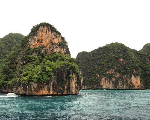 The Phi Phi Islands are located in Thailand , between the large island of Phuket and the western Andaman Sea coast of the mainland. The islands are administratively part of Krabi province in Thailand.